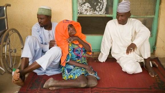 Hauwa'u Makada sits on the floor waiting for trichasis surgery with her brothers. Her wheelchair is nearby.