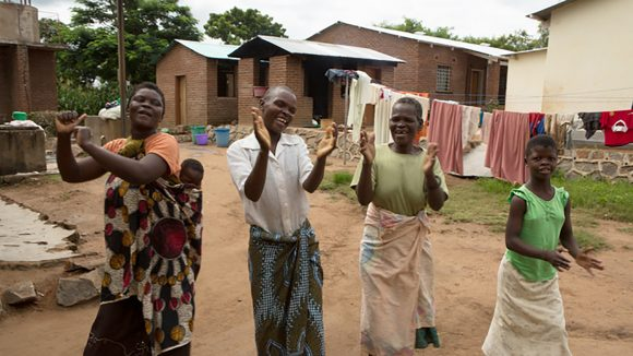 A group of women in Malawi sing, dance and clap.