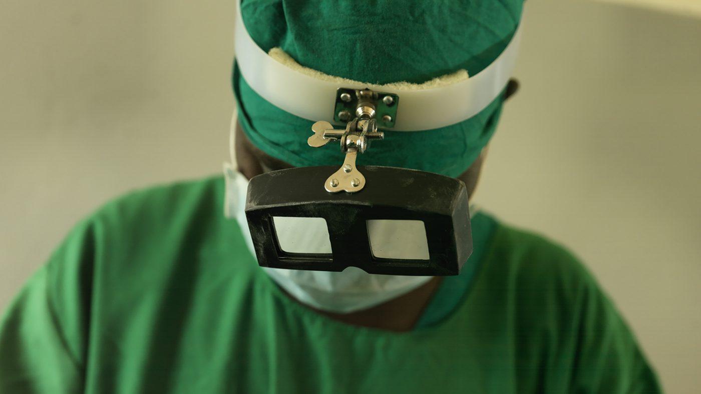 A trachoma surgeon wearing green scrubs.