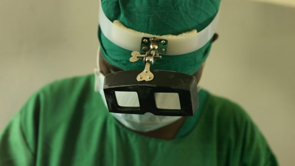A trachoma surgeon wearing green scrubs.