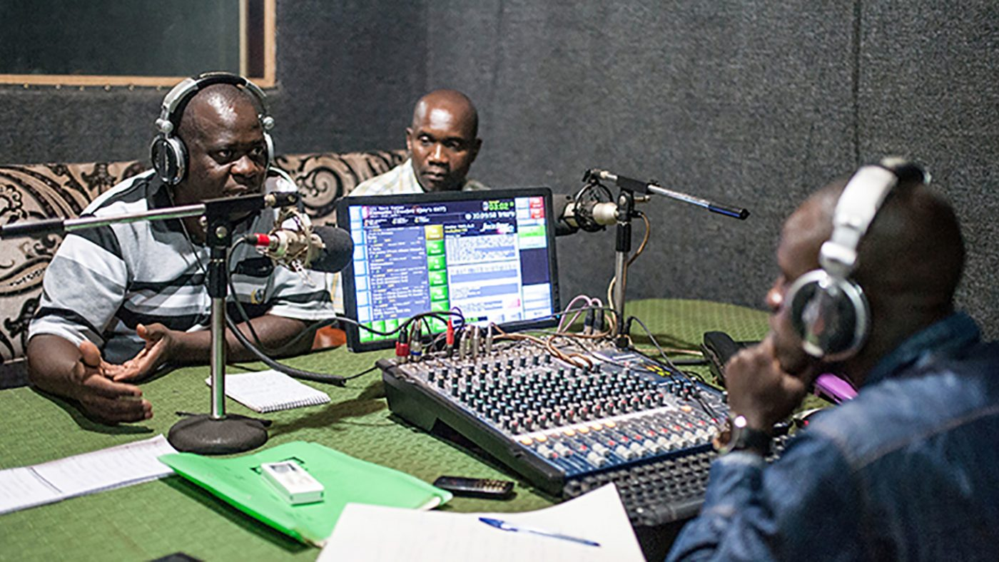 District onchocerciasis co-ordinator William Mugayo and Ugandan Secretary of Health Titus Ariyo discuss the mass drug administration project during a radio broadcast with DJ Robert Musasizi.