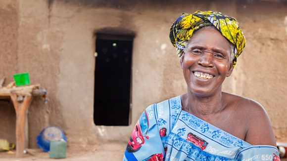 A woman smiling outside her home