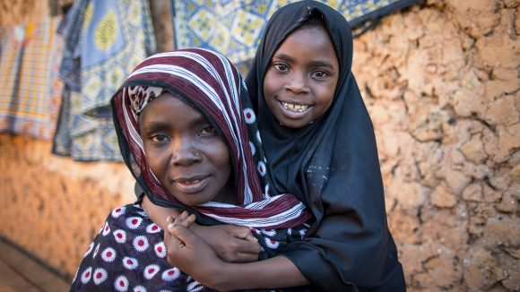 Young girl and mother sit outside their home