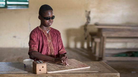 A boy with visual impairments sits in a classroom reading braille.