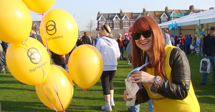 A girl wearing a Sightsavers tshirt next to Sightsavers branded balloons