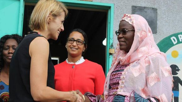 Delphine Skowron shakes the hand of a woman outside a school in Senegal
