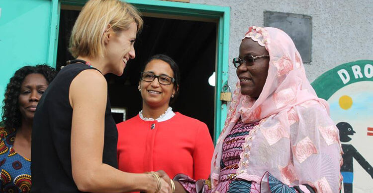 A representative shakes the hand of a member of staff outside a school in Senegal