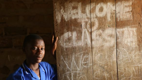 A girl standing in front of writing that says welcome to class