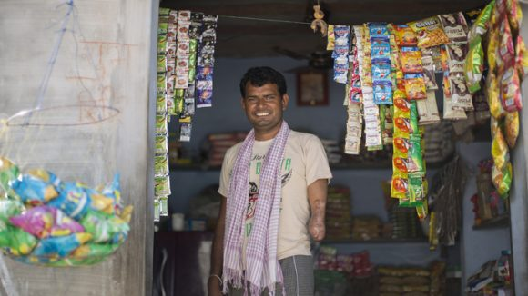 A photo from the Framing Perceptions exhibition featuring a man in India standing in the doorway of a shop, surrounded by packets of sweets hanging from ropes.