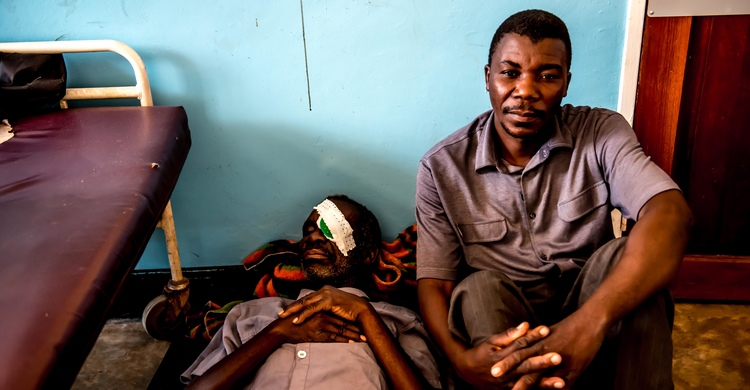 Peter Joseph lying on a bed in the men's ward after having had cataract operations, performed by Dr Gerald, one of Malawi's few eye surgeons. Nsanje Hospital, Nsanje, Malawi. Peter's son January (right) cycled him 12 hours to get to the hospital.