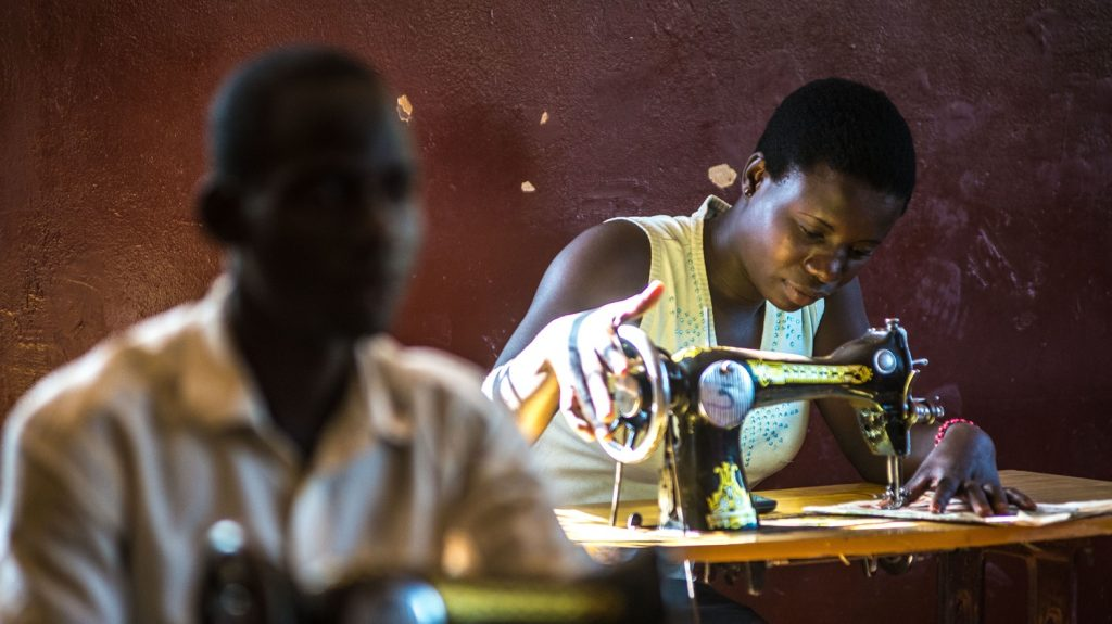 A young woman working at a sewing machine.