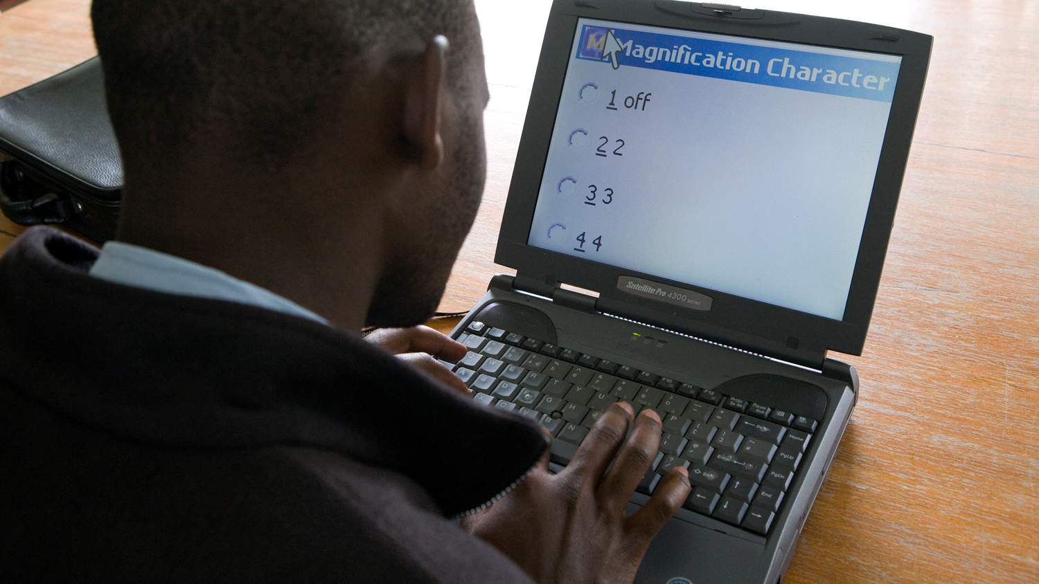 Man using a computer's built-in screen magnification options