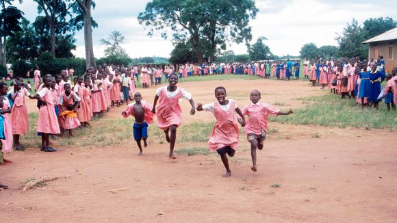 School children race together in Uganda.