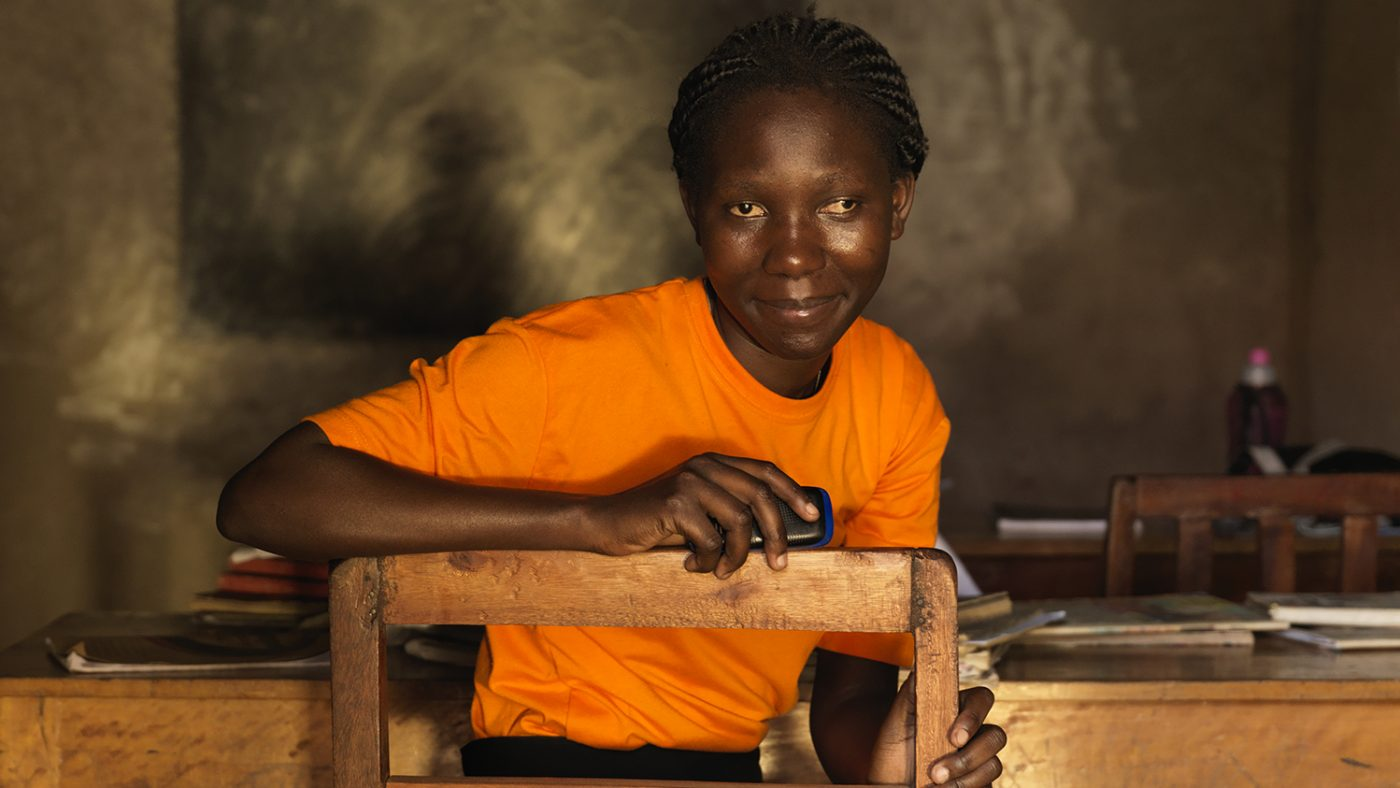 Harriet is sitting and leaning over the back of a chair. She is smiling and wearing a bright orange tshirt.