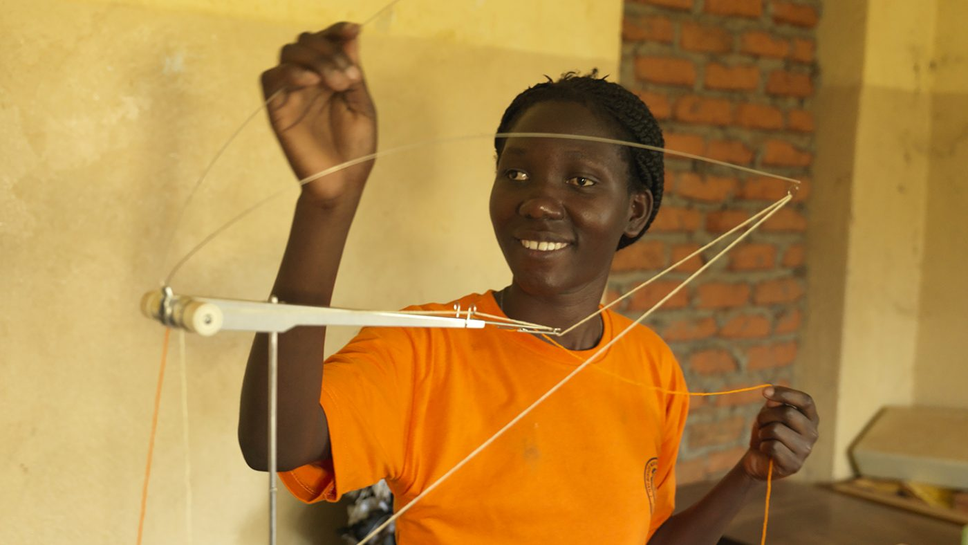 Harriet holding up a piece of string and smiling.