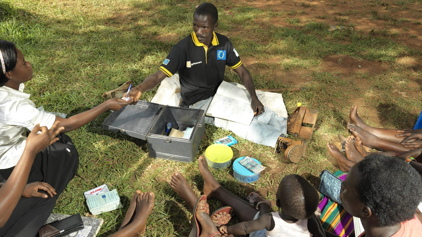 Joseph sits on the grass outside, with books over his lap, with the savings and loan group.