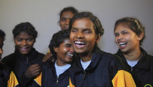 A group of visually impaired girls wearing Sightsavers tracksuits, laughing.