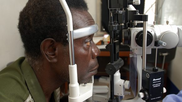 A man looks into a eye testing machine.
