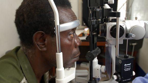 A man looks into a eye testing machine.