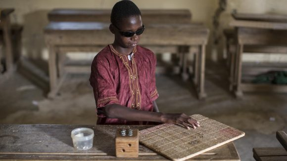 Boy using braille tablet