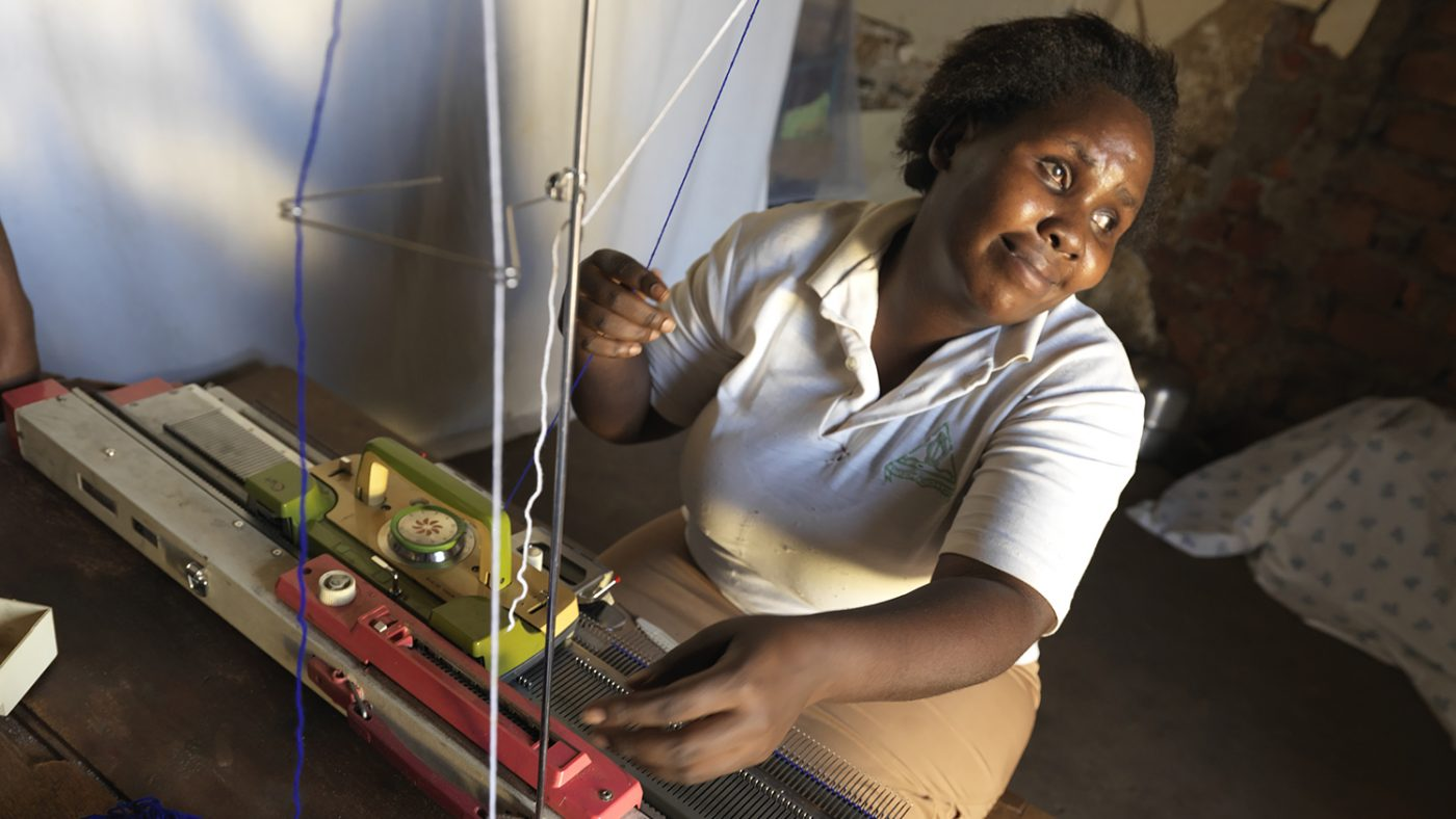 Rita sits, making jumpers on her knitting machine.