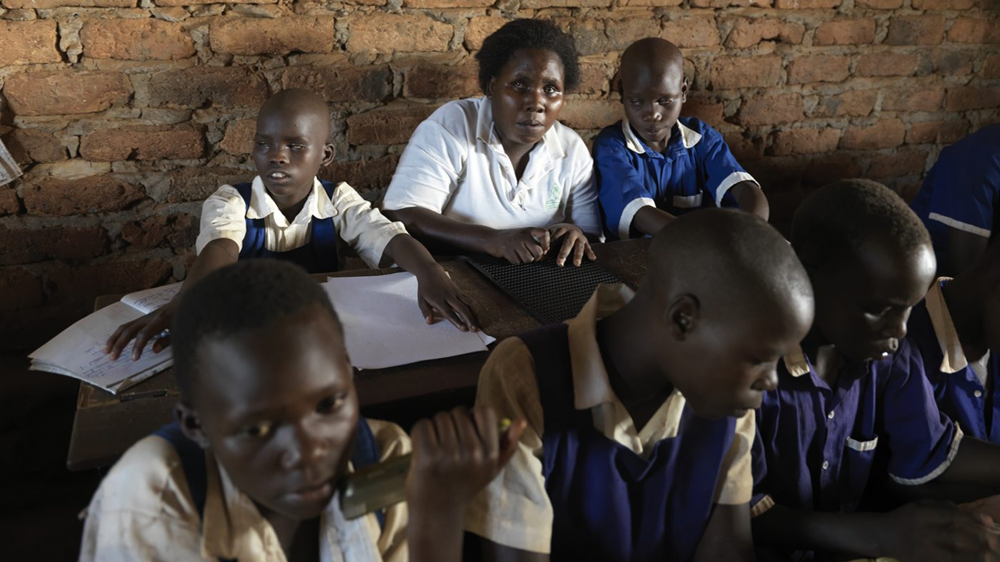 Rita sits with her visually impaired students in a classroom.