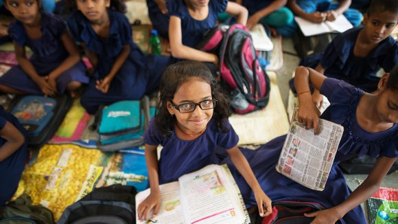 A girl with glasses smiles with a book on her lap.
