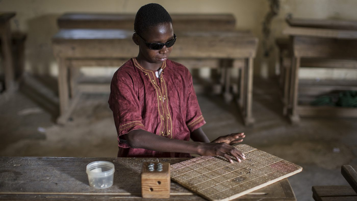 Mohamed sits in the classroom reading braille.