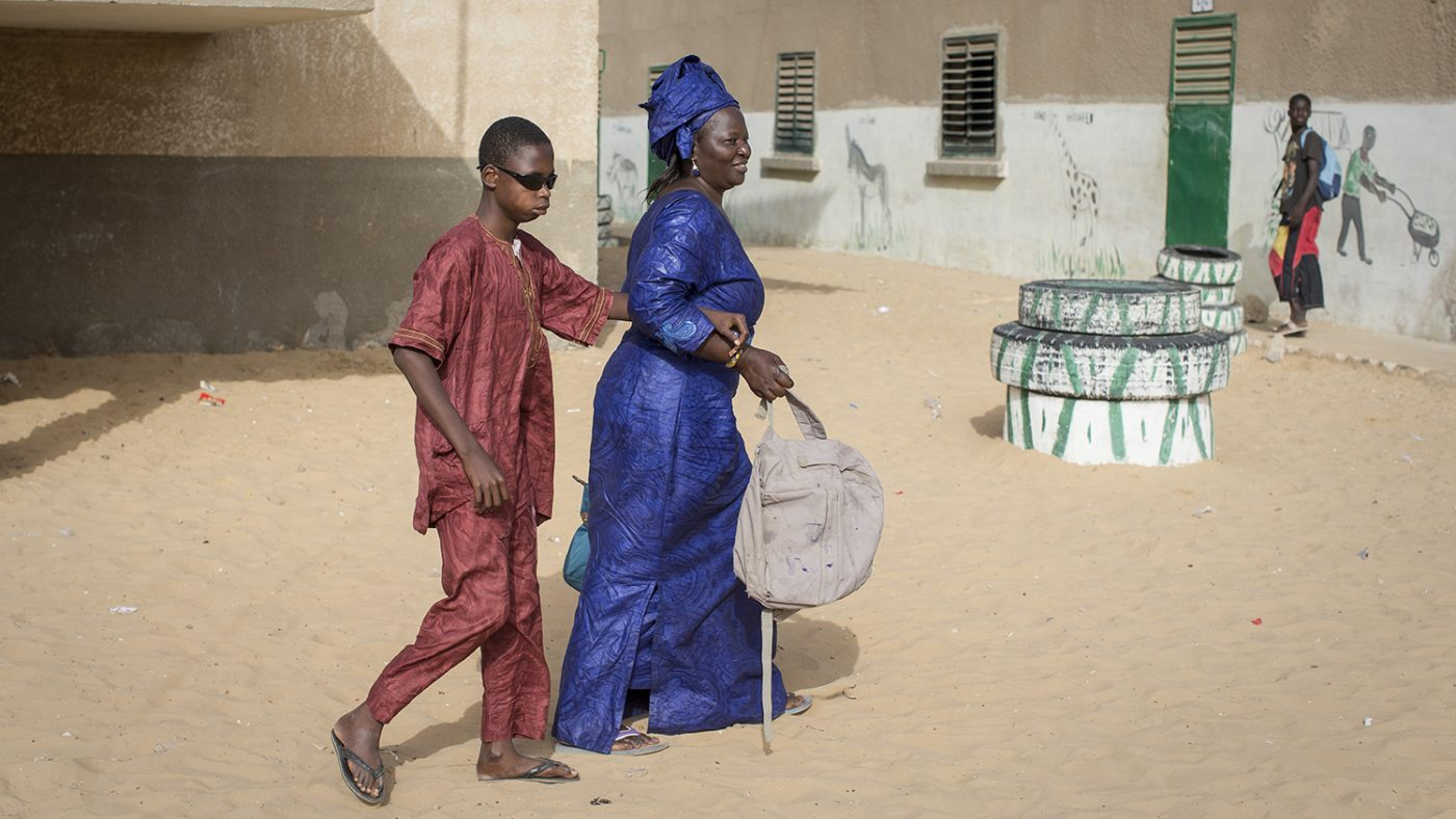 Mohamed walking with his aunt, Dione, who takes care of him.