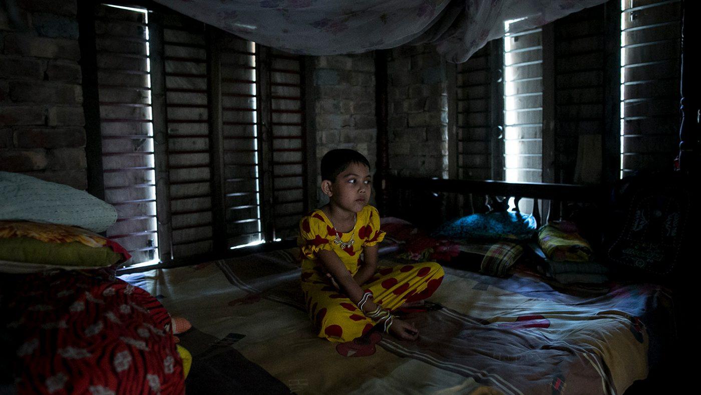 Muslima sits alone in the dark.