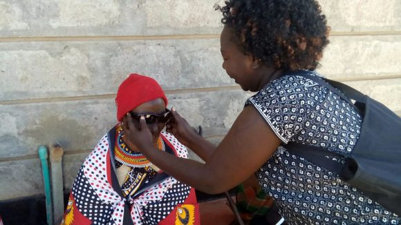 A woman is given sunglasses following cataract surgery in Kenya.