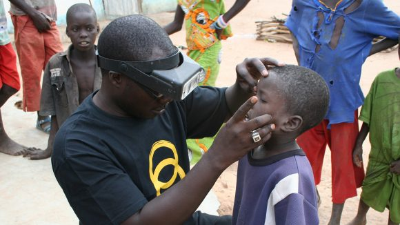 A boyhas his eyes examined by a health worker in Senegal.