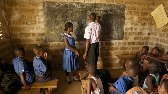 A crisp, clear image of classroom in Sierra Leone. The teacher stands in front of the blackboard with a pupil, while the other classmates look on.