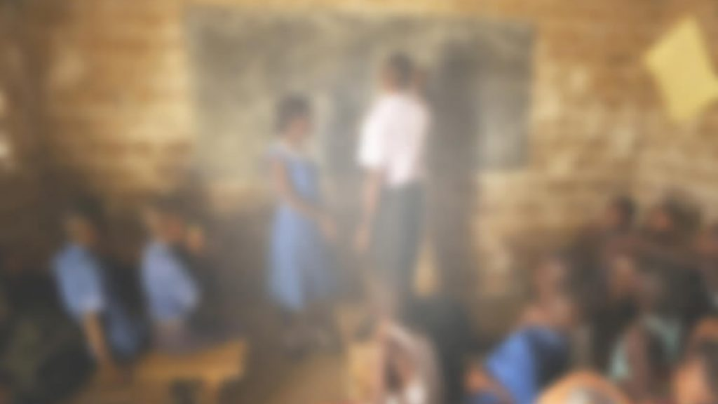 A blurry image of a classroom in Sierra Leone. The image is fuzzy and indistinct, with a whitish tinge. It's very hard to make out the teacher and the blackboard.
