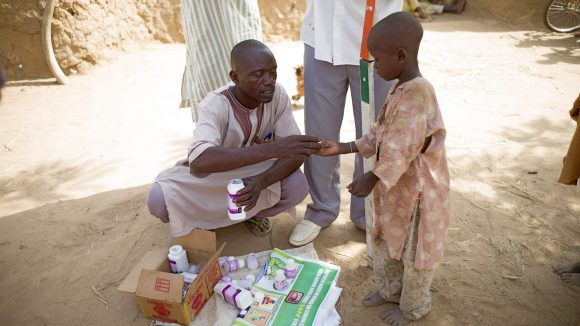 Community distributor Aliyu gives NTD medication to a young boy in Nigeria.