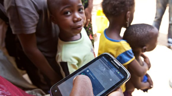 An eye health worker holds a mobile phone to record data, as a boy in the background looks on.