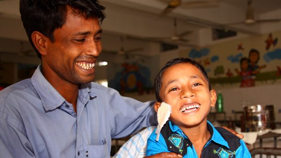 A boy smiles and is embraced by his father after having his dressings removed following eye surgery in Bangladesh.