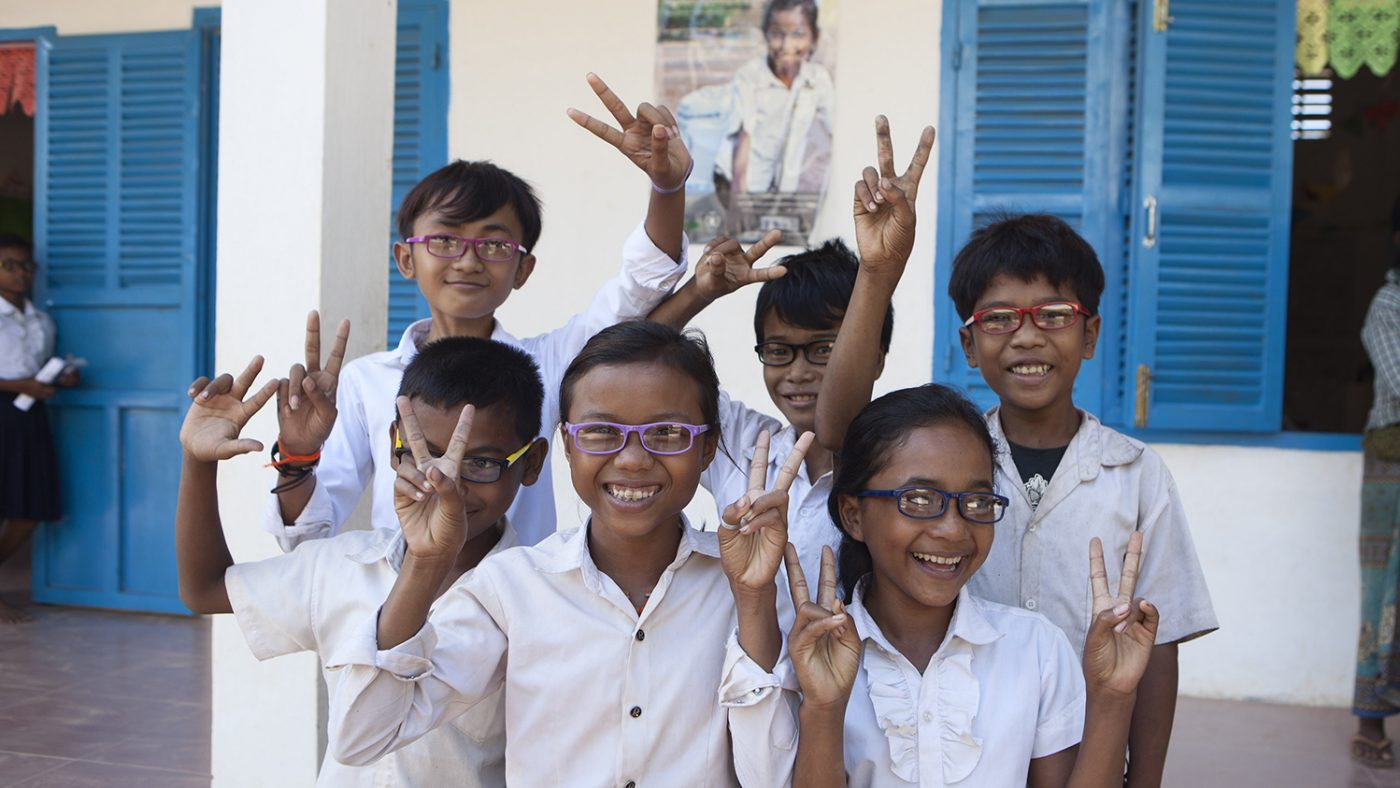 Six students smile and hold up peace signs with their fingers, all are trying on glasses.
