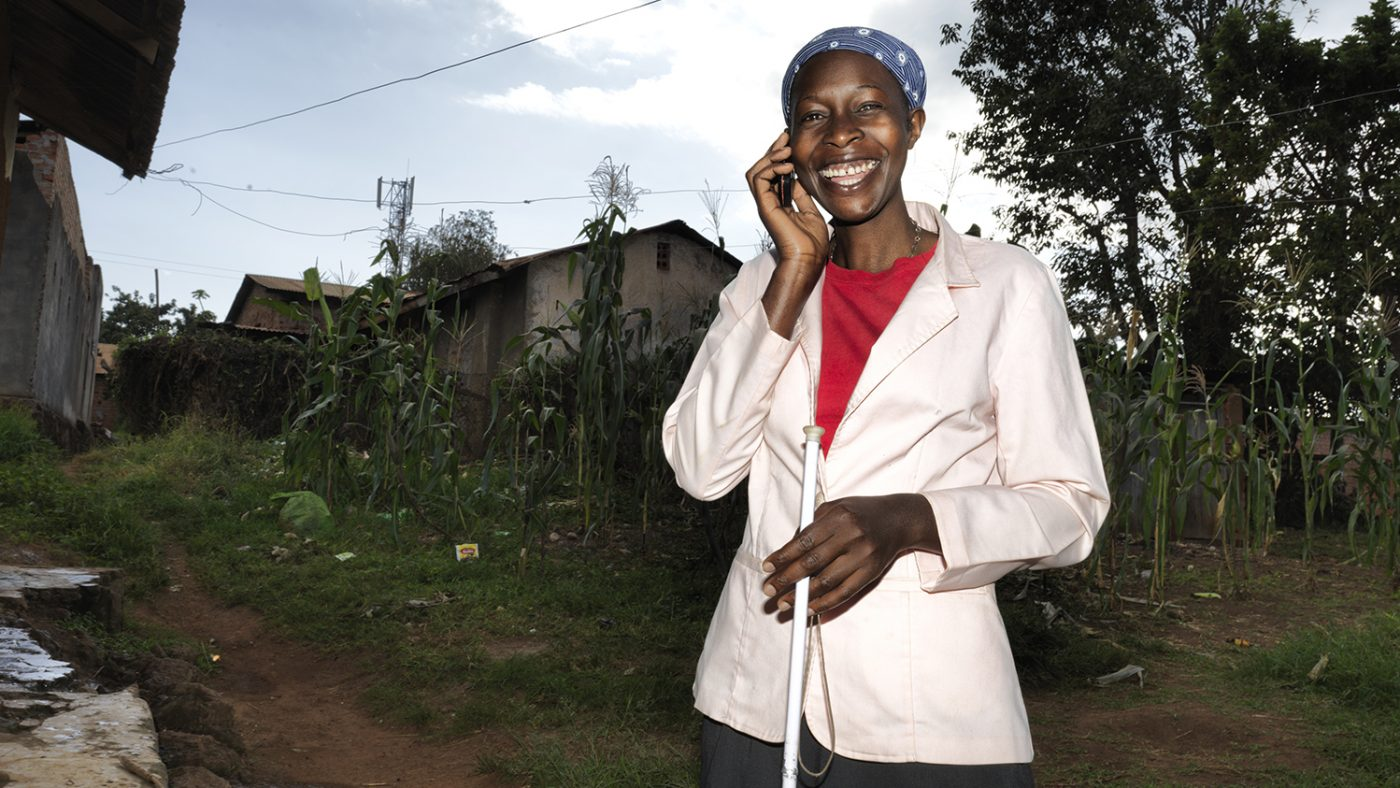 Sylvia smiling and talking on a mobile phone outside.