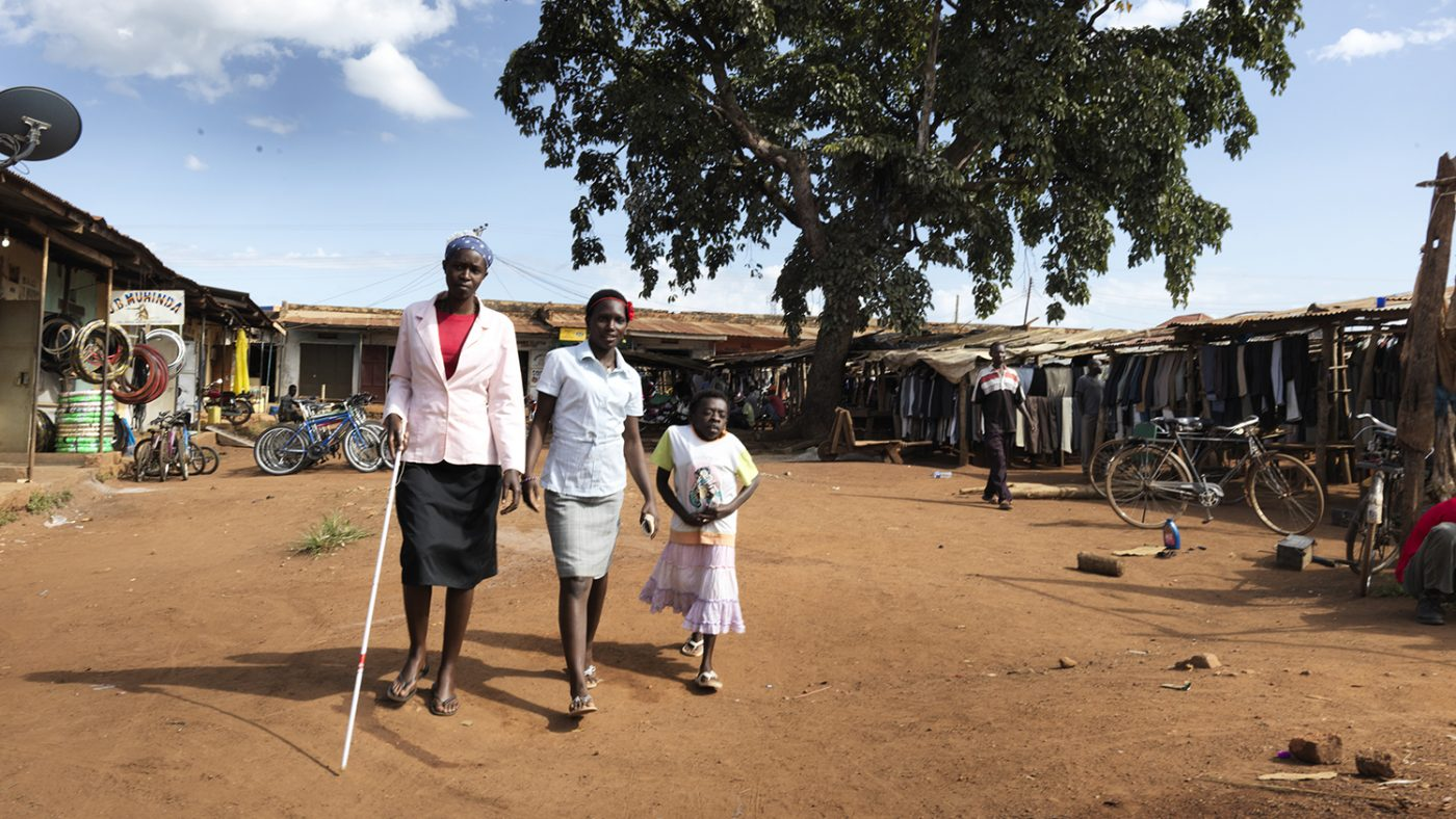 Three ladies are walking outside on a dusty road. Sylvia has a white cane.