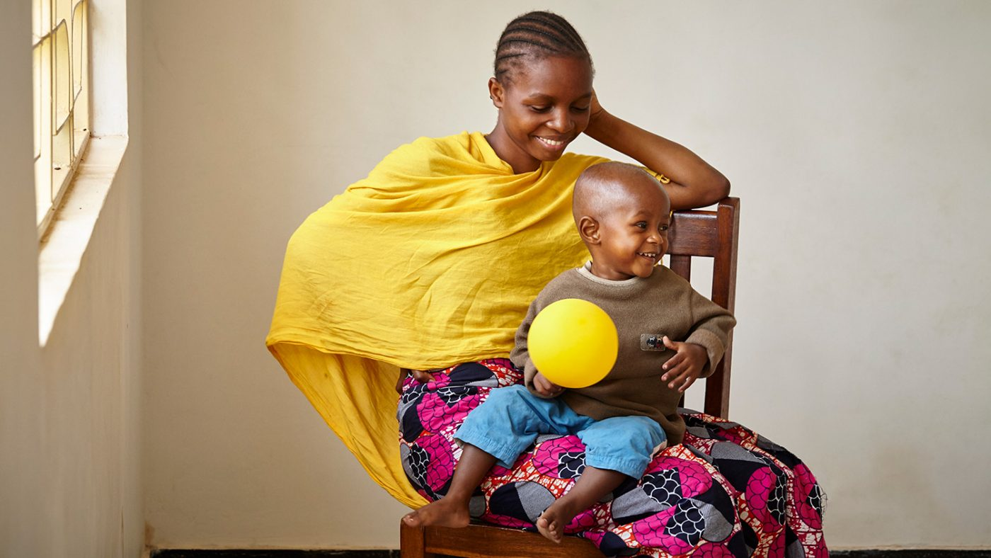 A woman sits on a chair with her young son on her lap; they're both smiling.