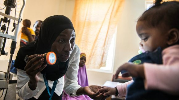A paediatric opthalmologist in Tanzania examines a baby.