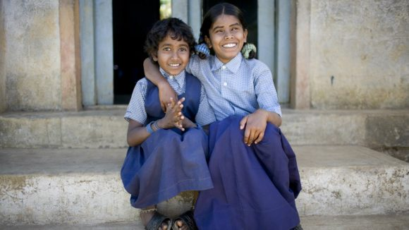Afsath, 10, visually impaired, sits with her friend on the school steps in India.