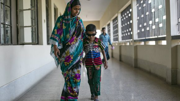 A child is guided by his mother after a cataract operation.