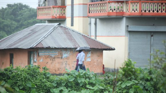 In Bangladesh people walk beside a delapidated house close to a hospital.
