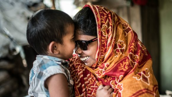 A smiling mother with a visual impairment hugs her young son.