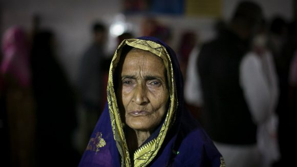 An older woman stands alone in Bangladesh.