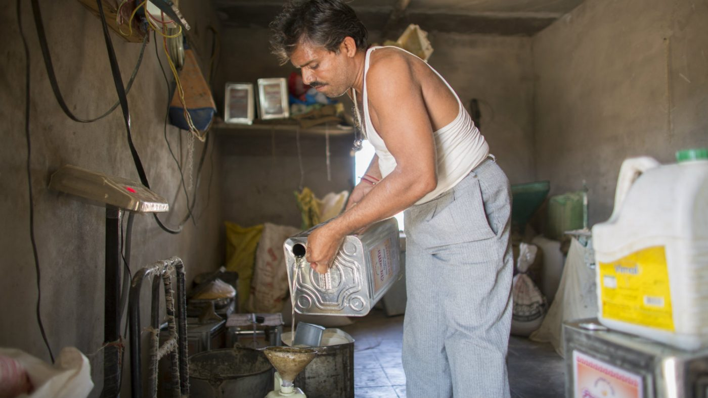 Bhagirath pouring oil for sale.