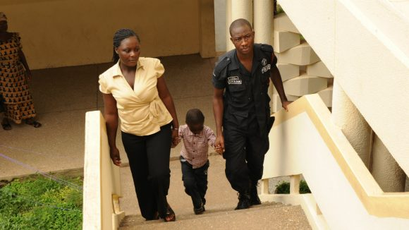 A visually impaired child climbs stairs helped by his mother and father.