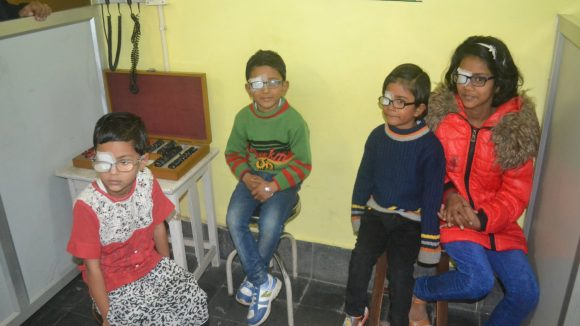 Four children sit and wait for treatment at the Sitapur eye hospital, India.